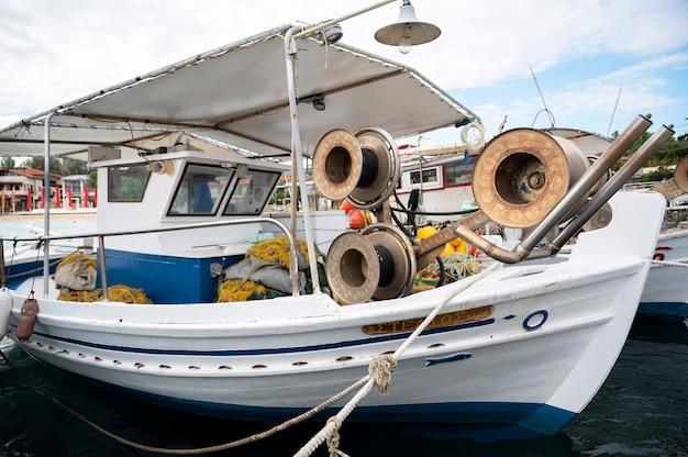 Швартованная лодка с множеством рыболовных принадлежностей в морском порту, эгейское море в ормос-панагиас, греция