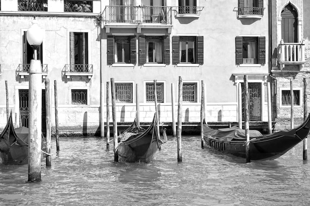 Moored gondolas in the grand canal in venice, italy. black and white image