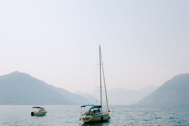 霧の中の山々に係留されたセーリングヨット