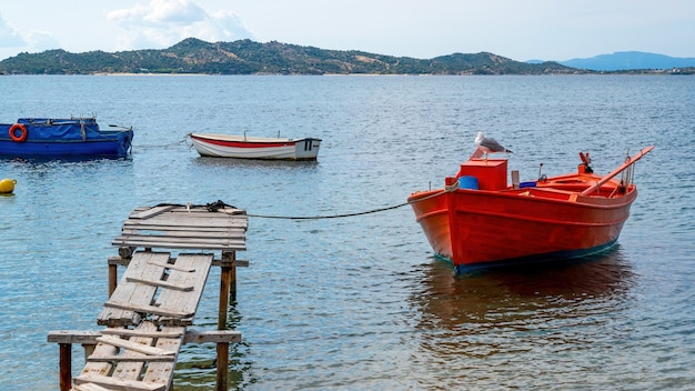 Moored wooden colored boats on aegean sea cost, wooden pier, yachts hills in ouranoupolis, greece