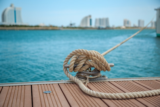 Mooring yacht rope with a knotted end tied around a cleat on a wooden pier