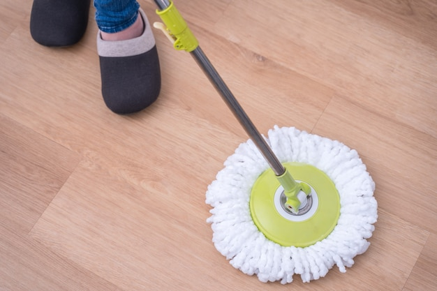 モップの床。モップ、クリーニングツール製品、抗菌の概念、ウイルス予防、クローズアップで自宅で木製の1階を洗う若い女性。