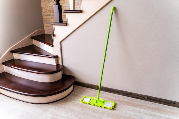 Mop with green microfiber rag, green plastic handle. cleaning gear near wall in room. stairs background.