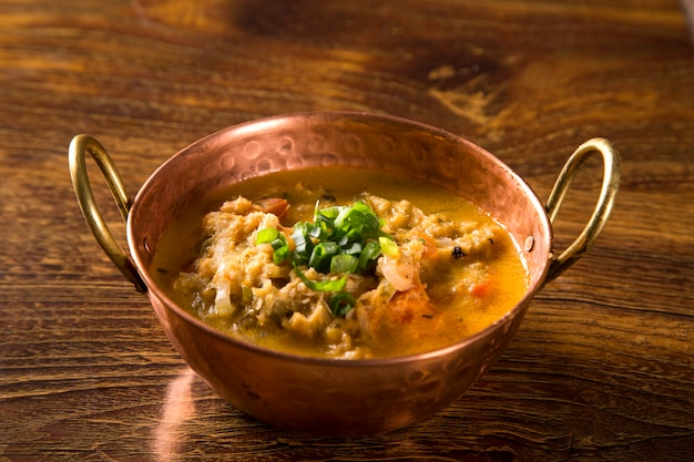 Moqueca, crab stew in metal bown.