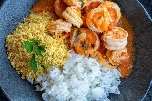 Moqueca de camarao - brazilian shrimp in coconut milk and palm oil. accompanies manioc flour and rice. bahia food.