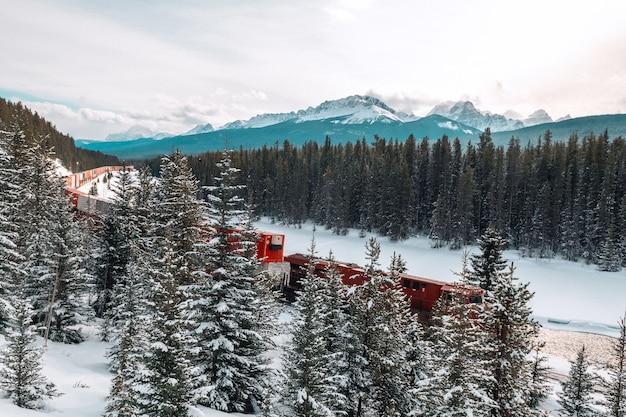 Кривая железная дорога моранта и поезд на фоне канадских гор роки