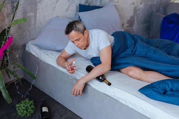より多くのアルコール。ベッドに横になってガラスを保持している悲観的な成熟した男の上面図