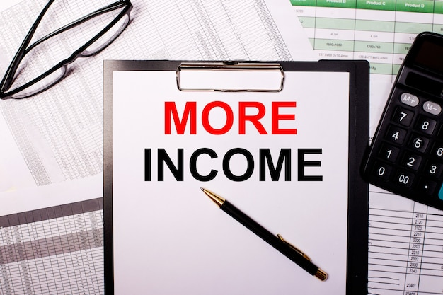 More incomeは、眼鏡と電卓の近くの白い紙に書かれています