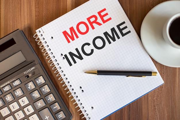 電卓の近くの白いメモ帳と暗い木製の背景に一杯のコーヒーで書かれたより多くの収入