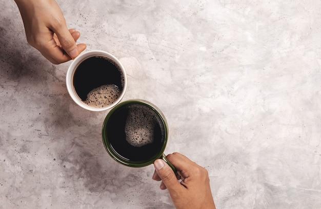 모링 음료 개념. 카페 또는 레스토랑에서 건배하기 위해 커피 한 잔을 들고 부부 또는 두 친구