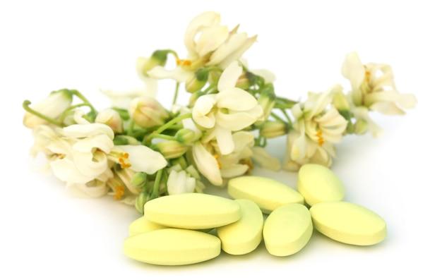 白い背景の上の丸薬とモリンガの花