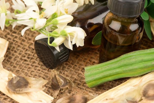 モリンガの果実、花、緑の葉、種子、白で隔離されたボトルに抽出されます。