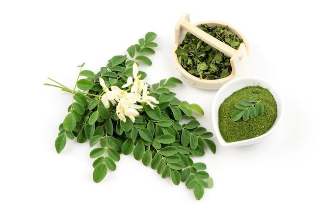 モリンガ緑の葉と白い背景で隔離の粉。