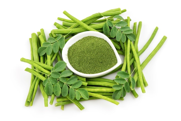 Moringa green leaves and powder isolated on white background.