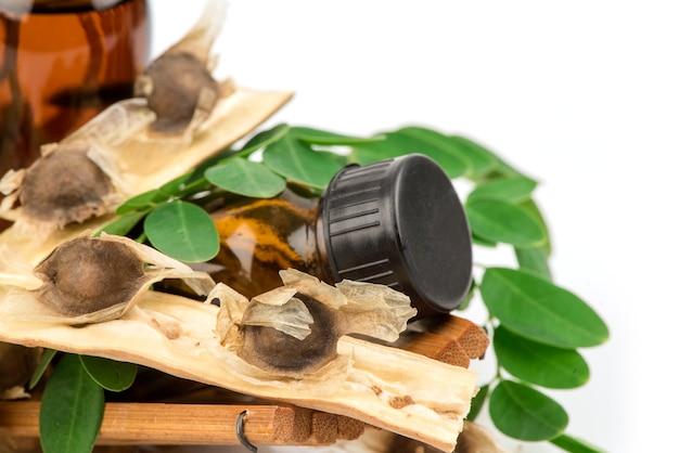 モリンガ緑の葉、種子、白で隔離されたボトルに抽出されます。
