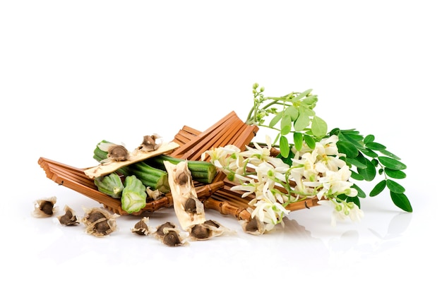モリンガ緑の葉、種子、花は白で隔離されます。