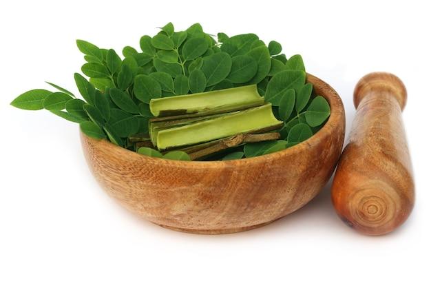 モリンガの葉と白い背景の上の樹皮と乳鉢の乳棒