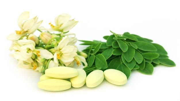 モリンガの葉と白い背景の上の丸薬と花