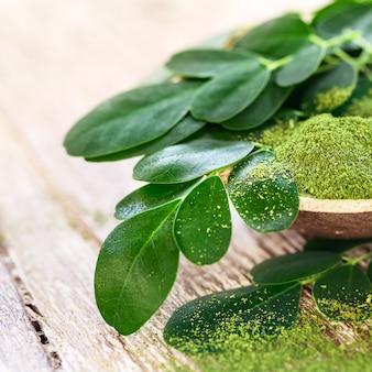 Порошок моринги (moringa oleifera) в кокосовой миске с оригинальными свежими листьями моринги