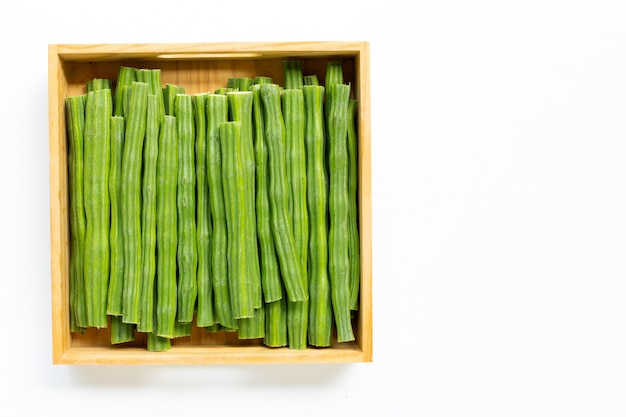 Moringa oleifera в деревянной коробке изолированной на белой предпосылке.