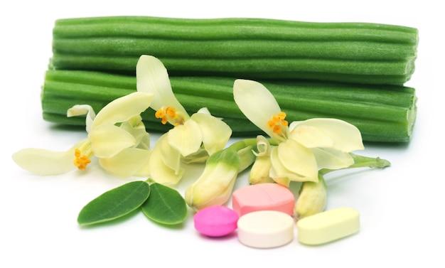 花と白い背景の上に葉を持つモリンガの丸薬