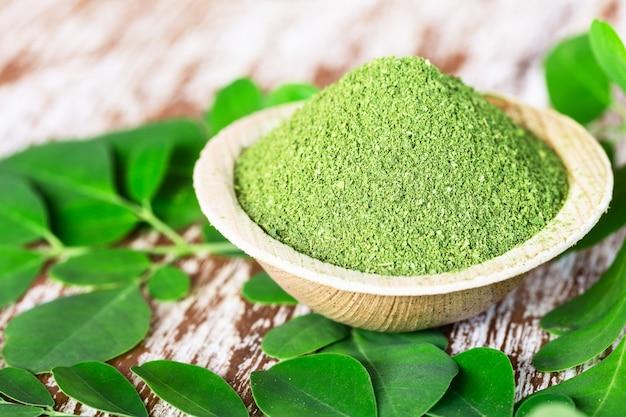 元の新鮮なモリンガの葉とココナッツボウルにモリンガパウダー(moringa oleifera)