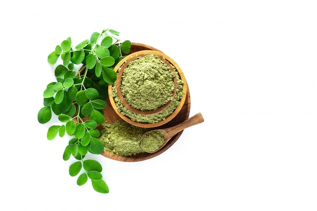 Moringa powder (moringa oleifera) in wooden bowl with original fresh moringa leaves isolated on white background.