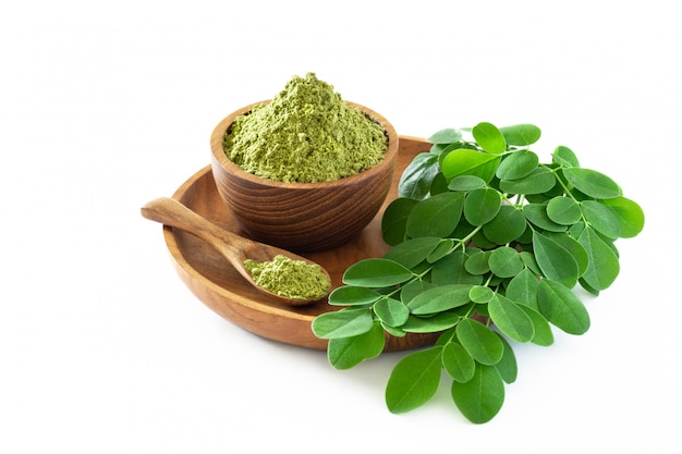 Moringa powder in wooden bowl with original fresh moringa leaves isolated on white background.