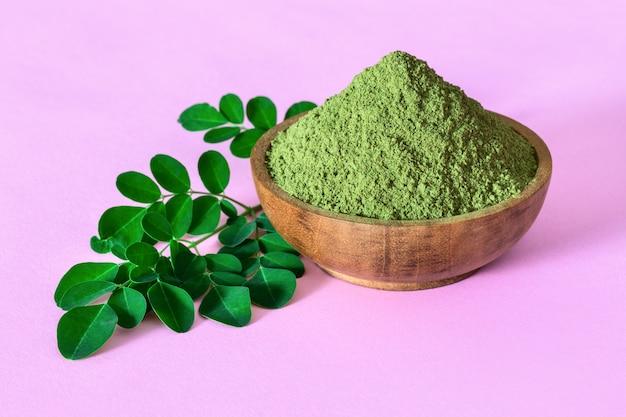 Moringa powder in wooden bowl with original fresh moringa leaves on pink background