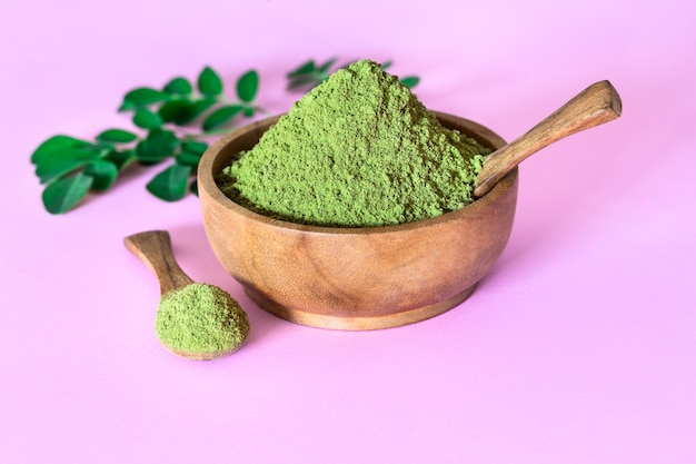 Moringa powder in wooden bowl with original fresh moringa leaves on pink background