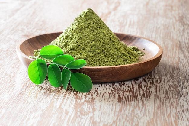 Moringa powder in wooden bowl with original fresh moringa leaves on rustic background.