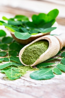 Moringa powder in wooden scoop with original fresh moringa leaves on wooden table close-up.