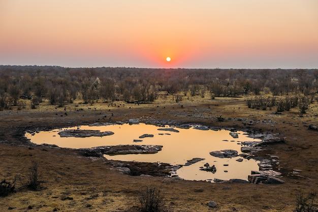 日没時のエトーシャ国立公園のハラリキャンプ近くのモリンガ滝壺