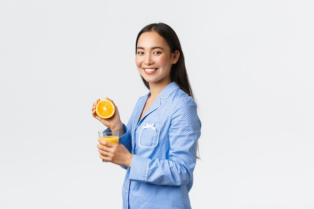 Утро, активный и здоровый образ жизни и домашняя концепция. профиль или красивая здоровая азиатская девушка в синей пижаме, выжимая апельсиновый сок в стекле и улыбаясь счастливым, начиная день право.