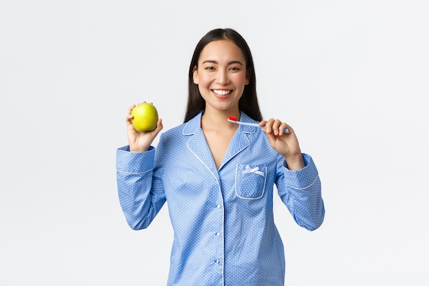 Утро, активный и здоровый образ жизни и домашняя концепция. улыбающаяся красивая азиатская девушка показывает зубную щетку и зеленое яблоко, имеет идеальные белые зубы и дает советы по гигиене рта, белый фон