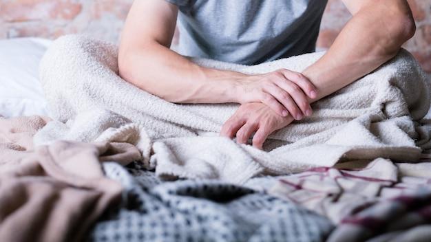 Снова утро. время просыпаться. человек сидит в грязной постели. руки сложены. стресс и бессонница.