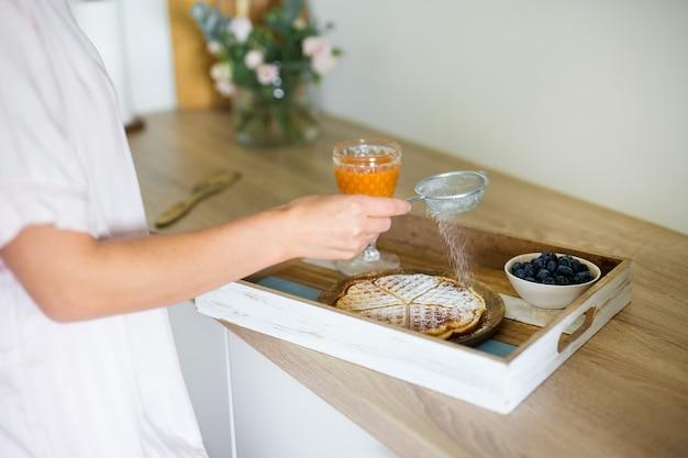 朝と朝食のコンセプト-木製トレイにベルギーワッフル、ベリー、ジュースのクローズアップ