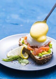 朝と朝食のコンセプト-サーモンとサンドイッチの準備、スプーンはそれにソースを注いでいます。