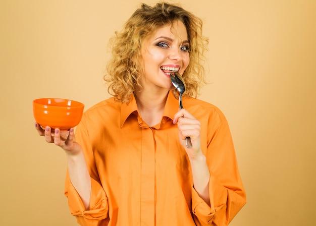 朝と食べ物のコンセプト。ボウルとスプーンで魅力的な女性。自宅で朝食。ダイエット、カロリー、健康的なライフスタイル。