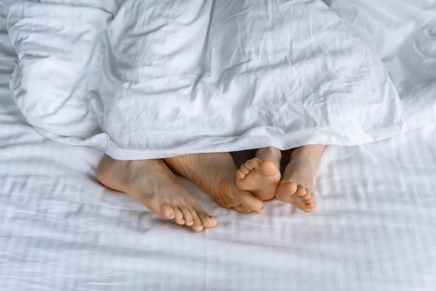 Утро и просыпание ног под одеялом в постели утром