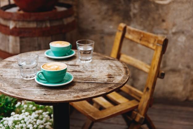 Утренний ароматный капучино с пышной молочной пеной сверху в двух керамических чашках бирюзового цвета со стаканами воды на круглом деревянном столе