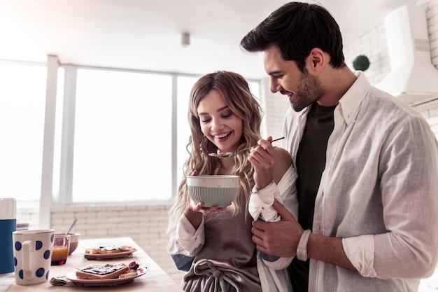 Утро дома. симпатичная длинноволосая молодая женщина и ее темноволосый муж выглядят довольными, проводя время на кухне