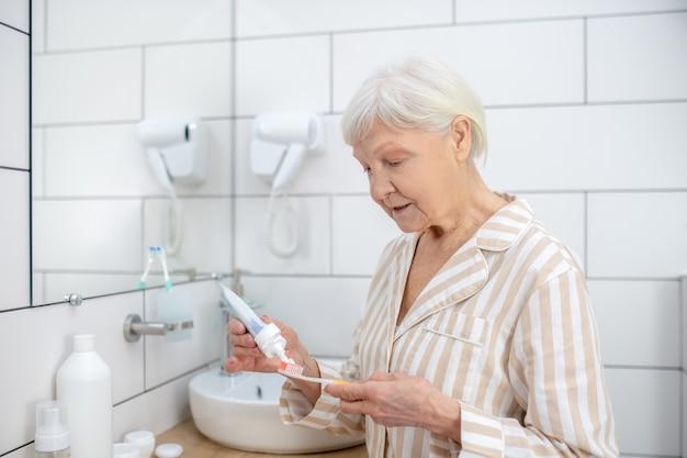 家で朝。歯磨き粉と歯ブラシを絞る年配の女性