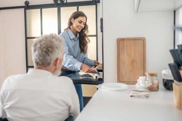 집에서 아침. 회색 머리 장애인 남자와 그의 젊은 아내가 부엌에서 아침 식사를 준비하고 있다