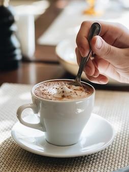 カフェでの朝。カプチーノとシナモンのカップ