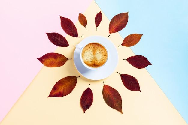 トリコロールテーブルの白いカップで朝秋のコーヒー。