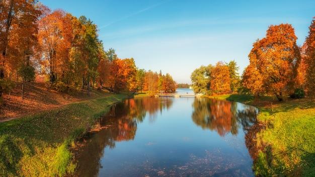 Утренний осенний пейзаж с озером и старым мостом. дворцовый парк. гатчина. россия. панорамный вид.