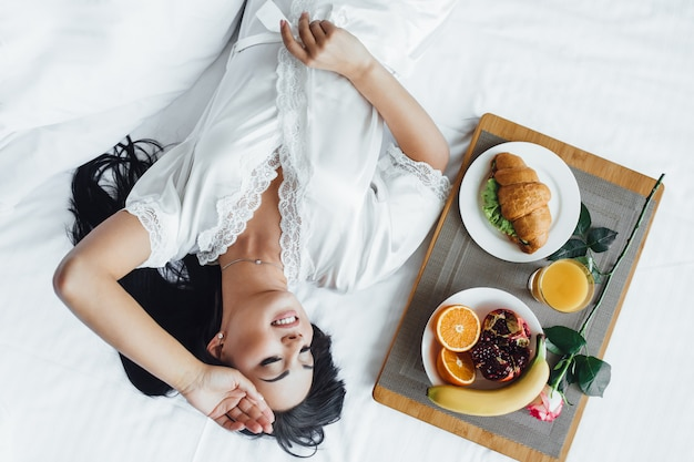 Morning of a beautiful girl in bed with food