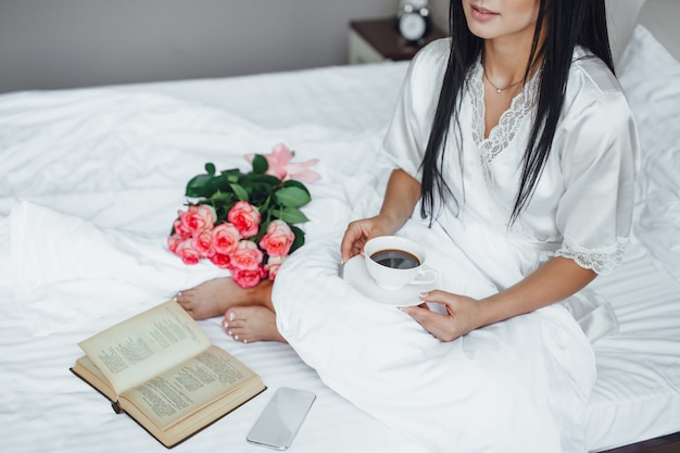 Morning of a beautiful girl with book and roses