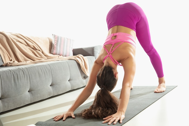 朝。自宅で灰色のマットの上でヨガの練習をしながら、屋内で運動する美しい若い女性。認識できない白人モデルの練習。健康的なライフスタイル、メンタル、マインドフルネス、バランスの概念。